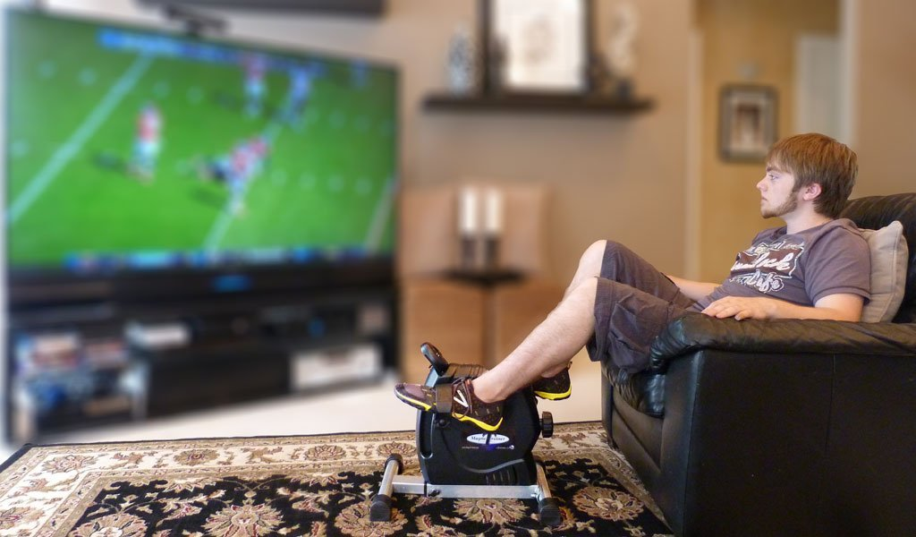 man watching TV and working out on the MagneTrainer-ER Mini Exercise Bike Arm and Leg Exerciser