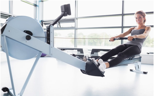 woman working out on a rowing machine to lose weight