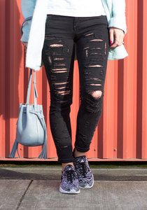 woman walking around with ripped boyfriend jeans with running shoes