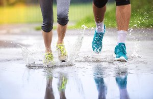 couple walking with wet running shoes in the rain