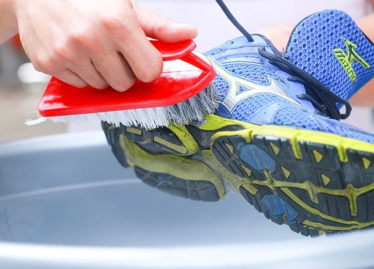 muddy shoes being cleaned with scrub brush