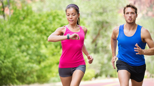 woman running and monitoring her heart rate monitor