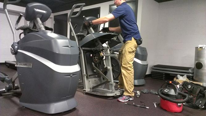 certified technician repairing a faulty elliptical